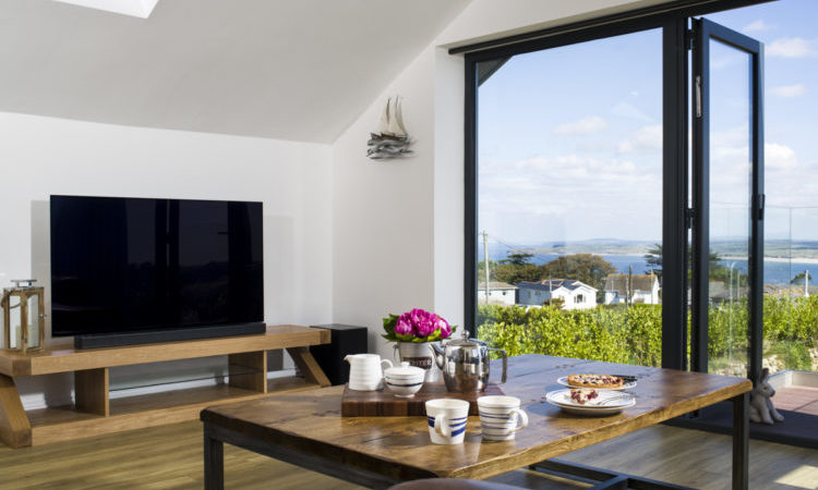 Modern living area with floor to ceiling doors looking out over coastal views in Cornwall - St Ives Cottage