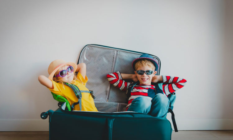 happy kids -boy and girl- enjoy packing and travel, family going on vacation
