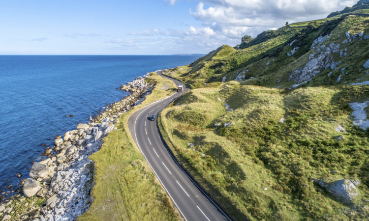 Causeway Costal Route with cars, a.k.a. Antrim Coastal Road on eastern coast of Northern Ireland, UK.
