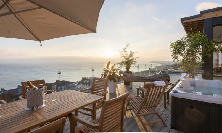 Sunset from the outdoor terrace of Skyfall villa in Sussex overlooking the coastal views with a hot tub and dining set