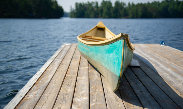 Green canoe rest on a lake wooden pier stock photo - slow travel